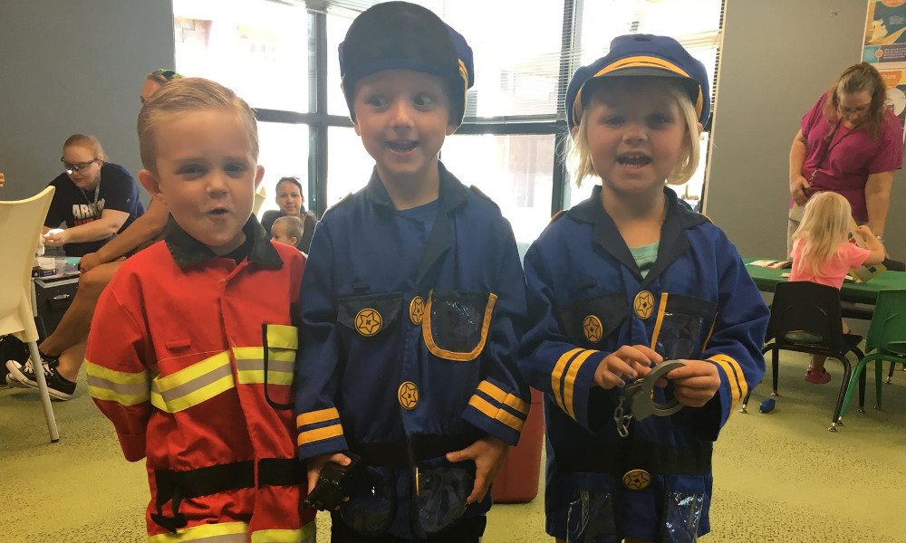 3 children dressed up as firefighters and police officers