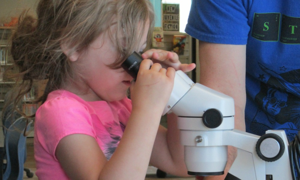 Girl looking at microscope
