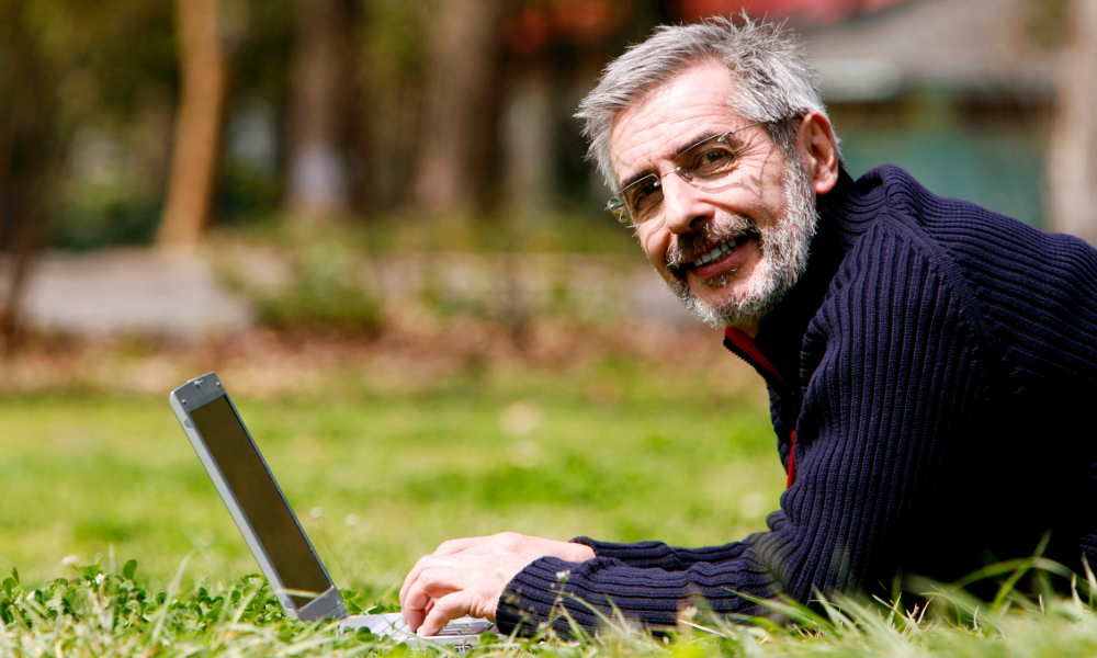 Man with laptop in grass