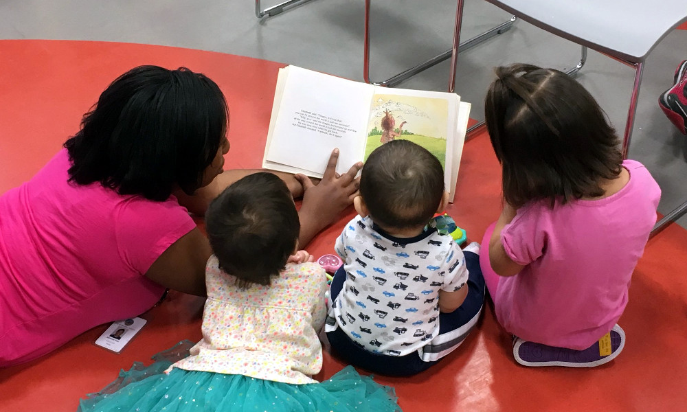 Woman reading to 3 children