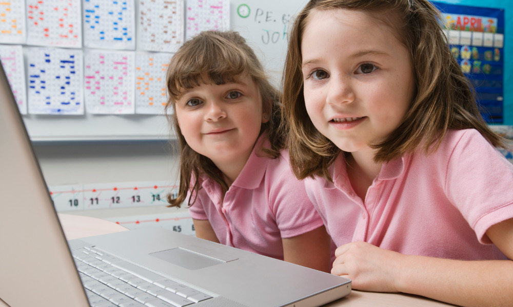 Two little girls in front of a laptop